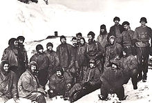 A group of men sitting closely packed together, in heavy winter clothes and wearing hats. Snow and ice on the ground and in the background