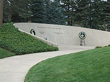 """An arching stone wall is set into a small grass-covered hillside. The wall is engraved thus: """"Lives Committed to God, Country, and Love"""", with two names engraved underneath, reading """"Gerald R. Ford, 1913–2006"""" and """"Elizabeth Bloomer Ford, 1919–2011 """". Two flowered wreaths are placed beside the names on stands."""