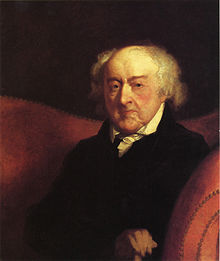 An elderly man sits in a red chair with his arms crossed, looking slightly left.