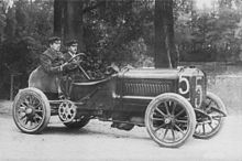An open-topped sports car, with the number 5 written on the front and side. A driver sits on the right side of the cockpit, and his riding mechanic sits alongside.