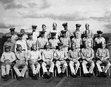 Twenty-eight Sailors in the uniform of the United States Navy pose on the deck of a World War Two-era Aircraft Carrier.