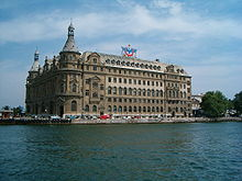 A Neo-Renaissance mid-rise structure with numerous windows, situated along a pure blue waterway