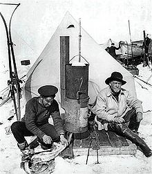 Two men sitting in front of a pointed tent; left-hand man in flat naval cap is skinning a penguin, right-hand man wears a wide-brimmed hat. Between them is a tall stove. Other equipment is visible in the background