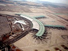 """Tilted aerial view of modern airport. Aircraft are parked next to """"arms"""" that extend from the central building"""