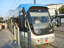 A blue and silver electrified tram stopped at a station
