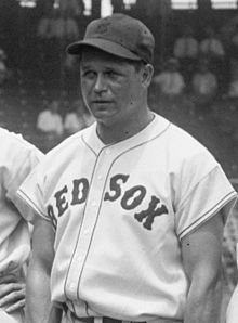 """A man is pictured from his belt up looking to the left of the camera. His button-down baseball jersey says """"RED SOX"""" across it and he is wearing a baseball cap."""