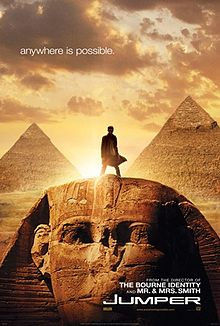 """Movie poster with the Egyptian Sphinx monument at the bottom of the image and two pyramids visible in the background. A man is standing on top of the Sphinx&squot;s head, facing forward. Sunlight behind him makes it difficult to see most details. The sky has multiple clouds, and at the top of the image is the tagline """"anywhere is possible."""" At the bottom of the image is the film&squot;s title and website for the film."""