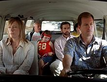 A film screenshot shows the family all seated in the Volkswagen Microbus as it is driven on a highway. The angle is from the windshield looking into the vehicle so that the majority of the interior can be seen. The mother is sitting in the front passenger seat with a dull expression on her face. The father is driving the vehicle with a smiliar expression. In the middle row, the daughter is looking down, listening to music from a CD player. Her uncle is seated on the right, looking to his left. In the back row, the grandfather is looking towards his grandson (who's face is slightly obscured by his father's head due to the angle). In the background, other vehicles can be seen driving on the highway.