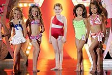 A film screenshot showing five girls standing on stage at the pageant at the end of the film. From left to right, the first girl (wearing a one-piece swimsuit) has her left leg placed in front of her right, the second girl (wearing a two-piece swimsuit) has her legs shifted in the opposite direction, at center the main character (wearing a one-piece swimsuit) is standing straight, the fourth girl (wearing a one-piece swimsuit) has her left leg placed in front of her right, and the last girl (wearing a two-piece swimsuit) also has her left foot forward. All of the girls are smiling towards different angles. The background of the stage is decorated and it is reflected on the shiny surface of the stage.