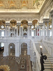 Tall hall with many arches. The vaulted ceiling is about 25 meters up and is lavishly decorated in a gold and red theme. Many white arches and pillars decorate the two stories. A marble staircase goes up, with a statue holding a globe aloft.