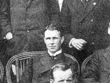 A man, fresh-faced with dark, brushed-back hair, seated among a group. He is wearing a naval officers uniform with a high, stiff collar