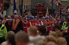 A street is occupied by men and women in formal uniform, some bearing flags, some bearing banners, some playing musical instruments.