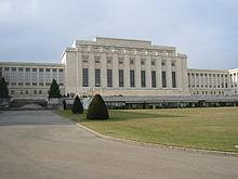 A drive leads past a manicured lawn to large white rectangular building with a columns on it facade. Two wings of the building are set back from the middle section.