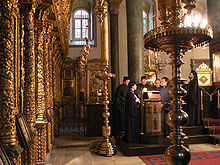 A group of priests gather in the background, outshone by copper-colored pillars and ornamentation in the foreground.