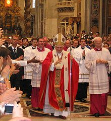 The present Pope, wearing robes of red and white, is walking in procession in St. Peter's, and raising his hand in blessing.