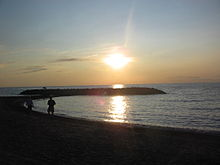 The sun setting over a darkened beach and breakwater.