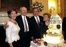 """Two men in suits are flanked by two women in formal dresses, standing beside a large birthday cake with lit candles and flowers. The cake is decorated with the text """"Happy 90th Birthday President Ford""""."""