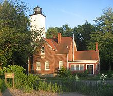 A brick house with a white, square lighthouse tower attached to the house.