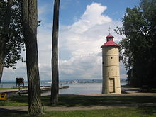 A small off-white lighthouse with a red roof and the trunks of two trees overlooking a bay with a city in the background.