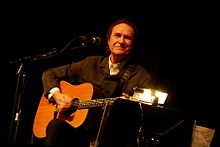 A man sits on a stool, smiling and facing the camera while playing guitar. He wears brown, and the background behind him is black.