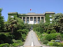 An ivy-covered neoclassical building atop a hill, with a greenery-adorned walkway leading to its entrance