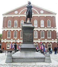 """A statue on a pedestal of a man standing with his arms crossed. An inscription on the pedestal reads, """"Samuel Adams, 1722–1803. A Patriot. He organized the Revolution and signed the Declaration of Independence."""" Behind the statue is a three story brick building with many windows."""
