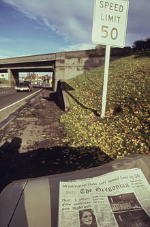 """A sign next to a highway says """"Speed Limit 50"""". A newspaper in the foreground has an article about the new speed limit."""