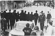 A line of police in the foreground facing some demonstrators/rioters in the middle distance in a city street.