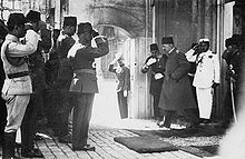 The sultan walking toward the palace exit as a number of men salute him