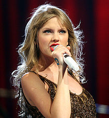 Taylor Swift, wearing a gold, sleeveless dress, sings into a hand-held microphone