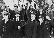 The Beatles are standing in front of a crowd of people at the bottom of an aeroplane staircase.