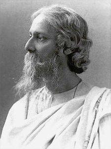 Late-middle-aged bearded man in white robes looks to the left with serene composure.