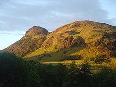 An irregular grass-covered mountain near sunset.