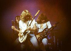 Gli Status Quo durante un concerto nel 1978. Da sinistra, Francis Rossi, Rick Parfitt e Alan Lancaster.