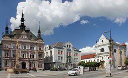 Turnov, náměstí Českého ráje, jemuž dominuje secesní budova městské spořitelny (1906); vpravo je raně barokní klášterní kostel sv. Františka z Assisi; mimo záběr, naproti spořitelně, je renesanční radnice, přestavěná r. 1894