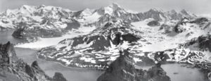 Aerial view of icy mountain-tops and valleys, water in foreground