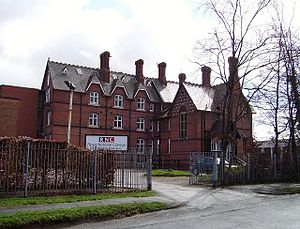 """A large brick building with a sign saying """"RNC""""; a fence and some trees in the foreground."""