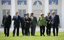 une femme blonde en vert au milieu des hommes en costume sombre