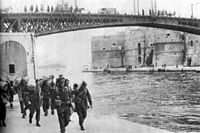 Soldiers carrying kit-bags approaching the photographer, while walking on a embankment next to a river with steel girder bridge in the background