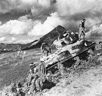 Camouflaged Sherman headed up a steep hill with troopers attending to the tracks