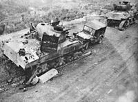 Two damaged tanks with their tracks visibly destroyed and a damaged Willy's Jeep displaying the 6th Armoured triangular flash