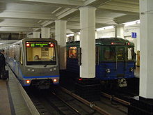 Two blue-and-gray trains—one new, one older—pulling into a station