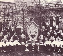 A sepia photograph with a large old structure in the background obscured by trees. In the foreground there is a large shield surrounded by five trophies. On either side of the shield stands 8 people.