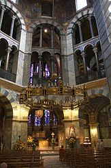 The interior of a tall octagonal church, rising in three rows of decorated arches. A large candelabra hangs above the central altar.