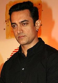 An Indian man wearing a black dress shirt.