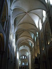 A tall wide church of grey stone elegantly vaulted with fine ribs.