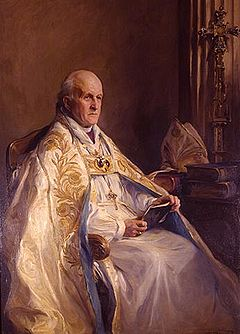 An elderly man with a solemn expression is seated in colourful robes, facing right. He is holding, but not reading, a book.