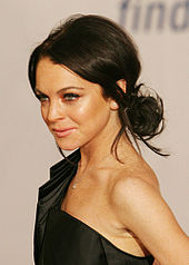A white woman with brown hair worn up wearing a black dress