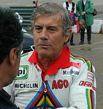 A man wearing a white leather top with writing on it. His arms are crossed and there is a man standing in front to his left.