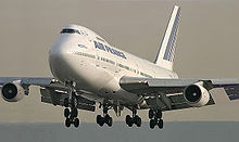 Aircraft front view with extended flaps and landing gear.